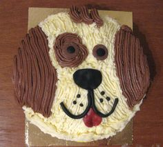 Puppy cake made from simple round chocolate cake, decorated with white and brown butter icing and royal icing for details.
