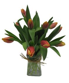 Ten tulips stems arranged in a square gathering vase with raffia tied around the vase.