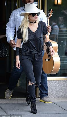 Country strong: Lady Gaga, 30, was seen leaving her New York City apartment Monday in her one-of-a-kind fashion as an associate trailed her with a guitar