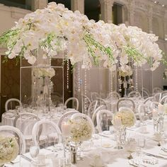#Centrepieces were #orchid-filled and accented with strands of #pearls and #crystals at this reception. Flowers were then placed on tall acrylic stands to create the illusion they were floating on air. We're in heaven! See more from this all-white wedding on WedLuxe.com today and in our new W/S 2016 issue that's on newsstands NOW! (: @ophelia_photography, decor design: @eclatdecor, floral design: @talaflorist)