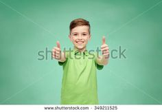 gesture, childhood, fashion and people concept - happy smiling boy in green polo t-shirt showing thumbs up over green school chalk board background