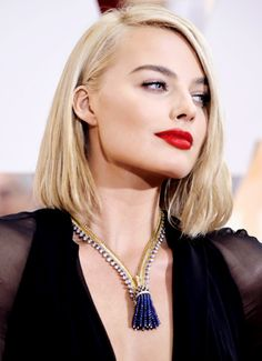 Margot Robbie's red lip goes perfectly with a little mascara and dark brows.