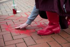 Delaney Cordova & Kent State University: The demonstration uses red sand in sidewalk cracks to represent those who have fallen through the cracks in our society. Those who are scarred and in plain sight but have no voice. Victims of human trafficking or modern day slavery. It's meant to be bright and eerie to spark people's curiosity that leads to them asking questions. The goal is to raise awareness and start a conversation to educate people on this tragedy that goes on in every country, every Sand Projects, Kent State University, Spark People, Human Trafficking, Curiosity, Rubber Rain Boots, Conversation, Goal, Sidewalk
