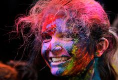 A tourist, her face smeared with color, smiles as she participates in Holi festivities in Kolkata, India, on March 8, 2012. (AP Photo/Bikas Das)