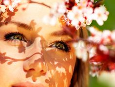 Stock image of 'Pretty female face with cherry blossom tree, closeup outdoor portrait'