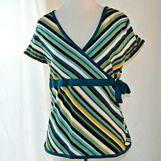 "New York & Company Striped Wrap Top Shade of teal, black, yellow and white striped top from New York & Company. Ties on the side to look like a wrap top. Some minor pilling and there was a tear in the sleeve that was stitched in white thread. Still in good condition!  | Measurements | Size: Large Length: 20.5"" Bust: 38"" Sleeve Length: 5.5""  
