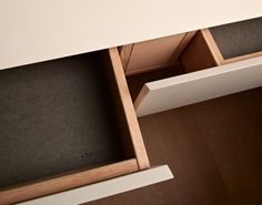 Custom made kitchen drawers with white exterior and wooden interior. Designed and made by German company Holzrausch.