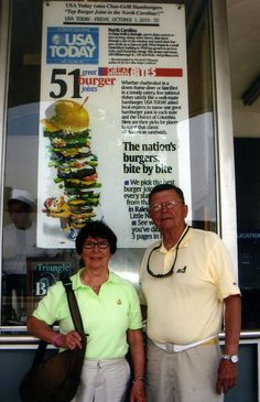 """Doris and Joe Lindner pose by the USA Today poster at the Char-Grill in Raleigh, N.C. During the past two years, the couple â€"""" retired doctors living on Hilton Head Island â€"""" have driven to all but one of America's """"51 Great Burger Joints†