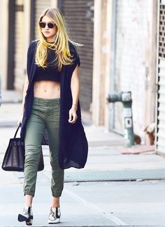 Gigi Hadid wears a crop top, black lightweight long sweater, army green cropped pants, Rodarte leather booties, and a leather tote