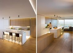 clean, wood on white. i like the black chairs and the lighting under the bar and cabinets.