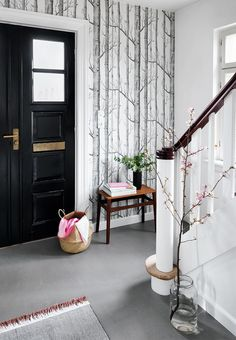 Amazing entryway! A wonderful grey linoleum floor and a cool graphic wallpaper welcomes you together with a vintage side-table and a branch from the nature.