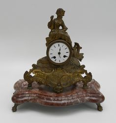 Relógio de mesa, em petit bronze, trabalhado em relevo, encimado por figura feminina, base em mármor