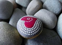 This stone has a happy feel to it. It feels GOOD in your hand. A pink-red glossy heart with white dots swirling from the inside out. It is a