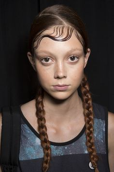 """DKNY Spring 2015 These pigtails were a throwback to '90s New York City. Eugene Souleiman used Wella Sculpt Force Gel ($14) to give bangs a wet """"baby hair"""" look."""