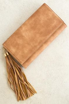 Maybe its a clutch, maybe its a crossbody! This versatile accessory can do both! You're sure to make the ultimate statement in this chestnut colored purse featuring double tassel for added emphasis! S