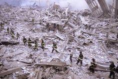 Bombeiros carregam mangueira entre as ruínas do World Trade Center, na Ilha de Manhattan, em Nova York.. Na manhã do dia 11 de setembro de 2001, dois aviões comerciais foram sequestrados no Aeroporto de Boston por terroristas da Al-Qaeda, e instantes depois atingiram intencionalmente as duas torres do maior complexo comercial do planeta