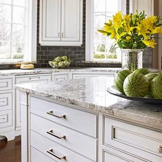 a great surface combo in the kitchen: stone countertops, white cabinets, nickel pulls, ceramic tile backsplash