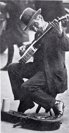 A busker with a banjo entertaining in Cathedral Square, Christchurch, 1927