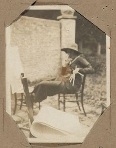 Virginia Woolf sits next to chairs holding folio-sized paper, undated.
