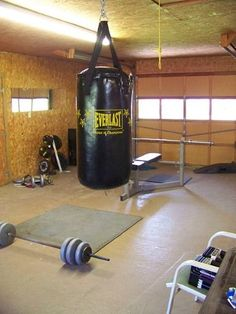 Garage gym pictures are expected to be overly simplistic or just plain terrible looking. A garage gym does not have to take up a lot of space. Neither does it have to have terrible conditions.  In this picture:      Flooring  Olympic barbells  Weight plates  Dumbbells  Weight bench  Boxing punching bag  Mirrors - Tap the pin if you love super heroes too! Cause guess what? you will LOVE these super hero fitness shirts!
