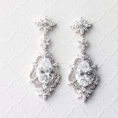Larger pear cut CZ jewels are set in a vintage-inspired drop design of sparkling marquise cut stones. An ideal choice for any special affair! They are 2.25 inches long and .75 inches wide with pierced post backs. Rhodium plated, grade AAA cubic zirconia, glass pearls and lead free.