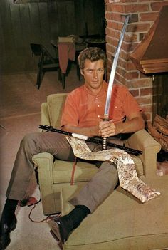 Clint Eastwood holding a katana at his home in the 1960s.