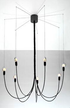 """Aufgeklappt wie eine Wäschespinne baumelt Tim Bautes Leuchter """"Seven Up"""" von der Decke und streckt seine sieben Fühler aus. Der Designer entwarf einzelne, nach unten zeigende Elektrokabel, an deren Ende je eine Glühbirne eingefasst ist. Drahtseile ziehen die Lichtquellen anschließend wieder Richtung Decke, so dass """"Seven Up"""" eine typische Kronleuchter-Form einnimmt. Preis: ca. 528 Euro."""