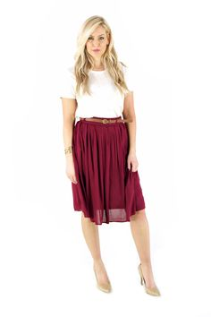 About me: Knee length pleated skirt with belt. Comes in Berry and Forest. Model is wearing: Small 100% Rayon How to take care of me: Hand wash cold. Do not bleach. Dry clean