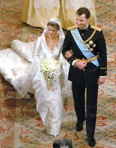 Letizia Ortiz. Princesse des Asturies épouse Felipe de Borbón, prince des Asturies. Pour le grand jour, elle portait une superbe robe créée par Manuel Pertegaz. Avec un col corolle, brodée de fils d'argent et d'or formant des fleurs de lys, des épis de maïs, des trèfles et des fraises, Letizia Ortiz était tout simplement sublime. La longueur de sa traîne ? 4,5 mètres, rien que ça !