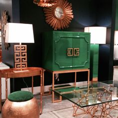 Emerald green and gold. I love the mixture of mid-century modern elements with Chinese designs and bamboo textures.  The glass top, atom coffee table & gold drum ottoman look like they should always be kept together, like a salt and pepper shaker. The stark black wall cozies up the hard lines, sleek textures, and colors.
