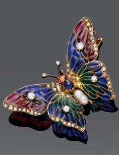 Enamel, pearl, diamond and gold butterfly brooch, circa 1900. The body set with one pearl and one cabochon sapphire, the wings applied with plique-à-jour enamel, set with four circular- and rose-cut diamonds. #ArtNouveau #antique #brooch