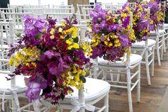 A decoração de casamentos feita por Vic Meirelles: os assentos da cerimônia brancos formam uma boa base para receber as flores de tons fortes como vermelho, amarelo e violeta.