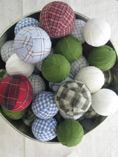 """Old plaid shirts are recycled into ornaments! Cut shirts into fabric strips ... wrap assorted Styrofoam balls ... hang with ribbon or pile into a bowl/basket. (I'd like to do this with some old plaid shirts from my dear farmer father. Great keepsake idea for any """"favorite"""" fabrics or garments!)"""