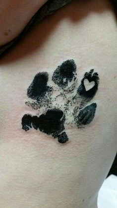 Beautiful realistic paw print tattoo with a heart inside