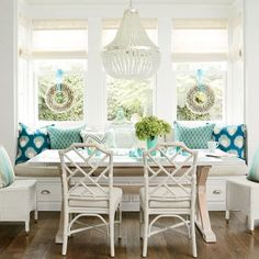 Combine Classic Patterns: In this cozy breakfast nook, soft blues and creams create a relaxed, beachy atmosphere. A mix of turquoise-and-cream pillows in pretty patterns take center stage here, accompanied by the hammered stainless steel and wood table and bamboo fretwork side chairs.