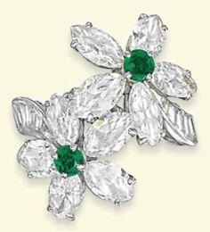 AN EMERALD AND DIAMOND RING   Designed as a pair of twin flowerheads, the petals mounted with marquise-cut diamonds to the circular-shaped emerald centres with tapered baguette-cut diamond shoulders to the plain hoop, with French assay mark for platinum