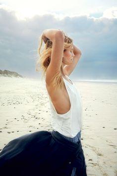 Poster une photo de soi au réveil pour montrer qu'on affiche déjà une mine full éclat en ouvrant les yeux, c'est le phénomène qui buzze sur Instagram. Découvrez nos 10 gestes qui rafraîchissent.  Photos: Gilles Bensimon  Mannequin: Constance Jablonski @Viva  focus: belle au naturel, no filter, jupe longue fluide bleue marine, top blanc, cheveux dans le vent