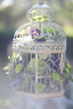 Bird cages can be simple or full of wonderful detail. We love the bright colors in a simple shabby chic bird cage.