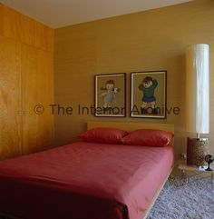 Grasscloth covers the walls of this bedroom and a pair of  cartoons from the 50s hang above the bed