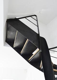Photo DH109 - SPIR'DÉCO® Flamme Mixte. Escalier d'intérieur métallique design sur flamme centrale formant escalier balancé sans mât central avec volée droite à l'arrivée. Escalier contemporain en métal et bois installé dans un appartement en duplex. Option rampe s'arrêtant sous plafond + Option volée droite à l'arrivée. Finition : acier brut patiné naturelle. - © Photo : Léo DELAFONTAINE