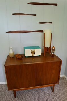 Sleek modernist fish wall art with a small credenza and well placed knick-knacks.