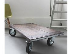 Industriële salontafel van steenschotten op grote geremde wielen. Afmeting: 112 x 70 cm.