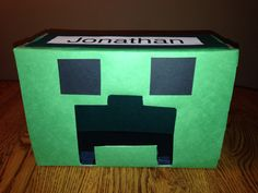 Minecraft Creeper Valentine Box Covered box with green paper, glued 2 square eyes of black paper & cut the Creeper mouth shape for the hole for treats. I put black paper inside to give the appearance of a black mouth.