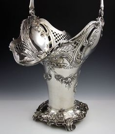 An impressive sterling silver basket with a swing handle, & a pedestal base & body designed with swags & flowers, 1900!