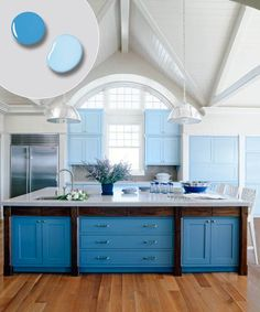 This deep-blue island takes center stage, while sky-hued cabinets define the perimeter and harmonize with the stainless-steel appliances and the island's bands of dark wood. Shown here: Behr's Sea Ridge and Tropical Pool. | Photo:John M. Hal | thisoldhouse.com