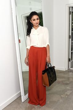 Vanessa Hudgens wears a pussy bow blouse with wide-leg pants, a Céline tote and gold jewelry