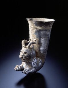 Silver with vitreous paste inlay, 5th-4th century B.C.E. H. 17.5 cm.   The rhyton with an animal protome-a horn for liquids to which the depiction of the forepart of an animal was attached, at a right angle-was a vessel form that came more widely into use in the Near East during the Achaemenid period (about 538-331 B.C.). The protome of this rhyton depicts the forequarters of a fantastic hybrid creature, a leonine beast with curved blunt horns and upright ears, probably meant to represent a…