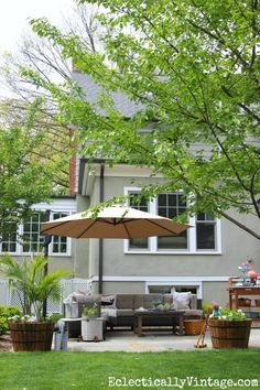 Backyard patio oasis - love the sectional sofa, plant stand turned bar cart and the giant cantilevered umbrella eclecticallyvintage.com
