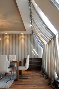 fenêtre de toit avec rideaux et voilages assortis au papier peint dans la salle à manger sous les combles