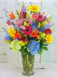 Traditional display of assorted spring flowers in brilliant colors. This is a real show stopper and attention grabber. Included in this bouquet are Snapdragons, Gerbera daisies, Roses, Larkspur, Lilies, Hydrangeas and many more favorite...
